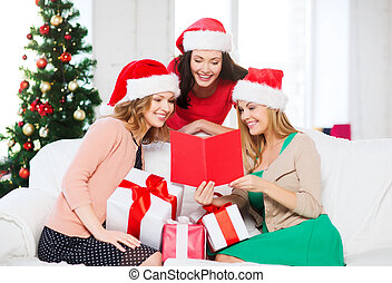 women in santa helper hats with card and gifts - christmas,...