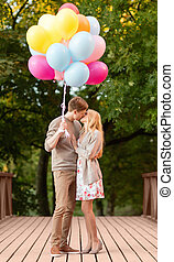 couple with colorful balloons kissing in the park - summer...