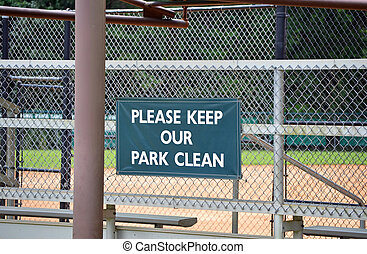 Keep Park Clean - A green sign on a fence reading Please...