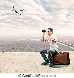 young man using binoculars at the airport - young man...