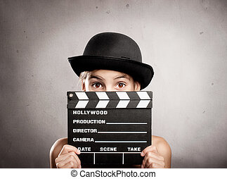 little girl holding a movie clapper board on a grey...