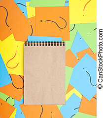 blank notebook on pile of colorful paper notes with question marks