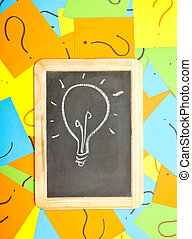 A lightbulb drawn on a chalkboard lying on a pile of...