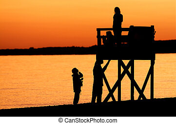 Golden Sunset on a Cape Cod Beach - The silhouettes of...