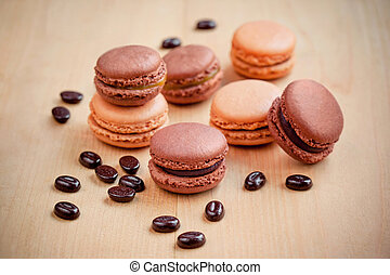 chocolate and caramel macaroons on wooden table - dark...