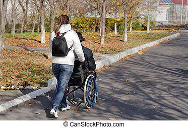 Carer taking a disabled man for a walk - Female carer taking...