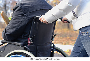 Woman pushing a disabled man in a wheelchair - Close up view...