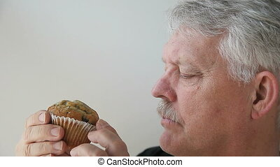 man eats blueberry muffin - older man eating his breakfast...