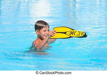 The boy with flippers for swimming in the pool