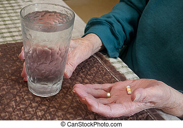 Elderly Woman with Pill - An elderly woman about to take a...