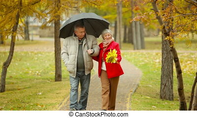 Date Under Rain - Senior couple having a rainy day date
