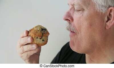 man has a muffin with coffee