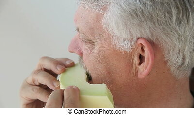 man eats slice of melon - senior man eating fresh honeydew...
