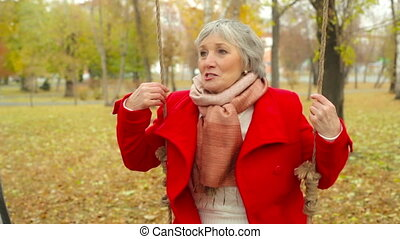Back And Forth - Close-up of an elderly woman swinging back...