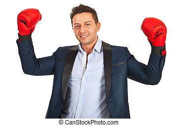 Victorious business man showing hands in boxing gloves...