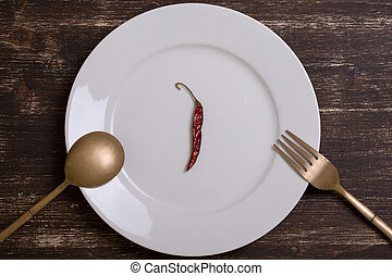 Red pepper on an empty plate with fork and spoon