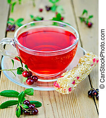 Tea with granola and lingonberries - Tea in a glass cup with...