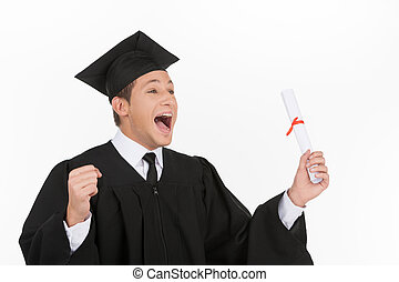 Happy grad. Happy young men in mortarboard holding diploma and gesturing while isolated on white