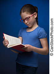 Pretty schoolgirl. Pretty little girl in glasses reading a...