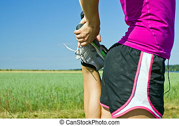 Woman runner stretching outdoors - Woman running on country...