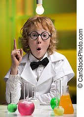 I have an idea! Happy little boy in lab coat gesturing while...