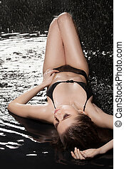 Wet beauty. Beautiful wet women in black bikini lying on the...