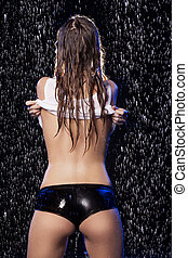 Wet beauty undressing. Rear view of beautiful young women in...