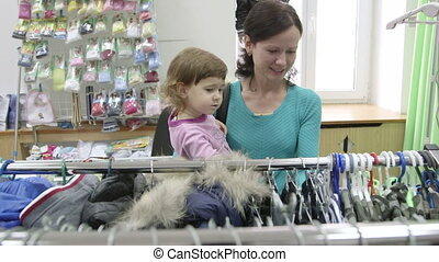 Clothing Store - Mother and daughter choosing clothes in...