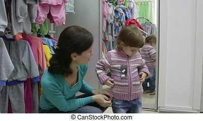Trying On Children Clothes - Mother with little daughter...