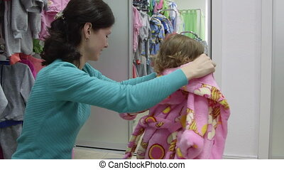Trying On Clothes in Clothing Store - Mother with child...
