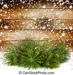 Snowy pine branch on the background of the old wooden walls