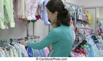 clothing store - Mother with child looking for clothes in...