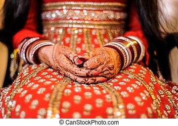 bride's hand with henna and bangles, punjabi wedding -...