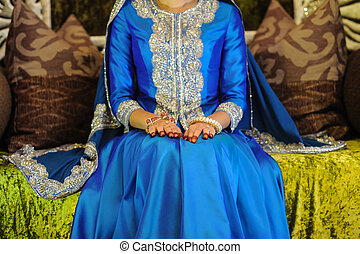 Bride Wearing a blue dress sitting on an altar, head not...