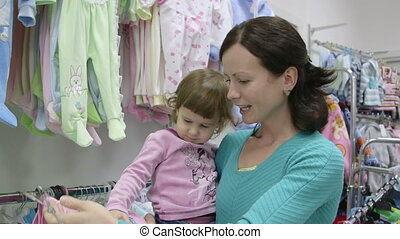 clothing store - Happy mother with child looking for clothes...