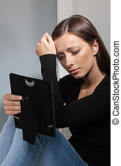 Break-up. Depressed young women holding a photo frame and...
