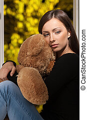 Women with teddy bear. Depressed young women sitting in...