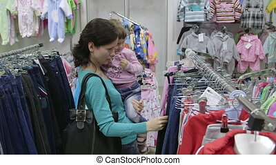 Customer at Clothing Store - Mother with child looking for...