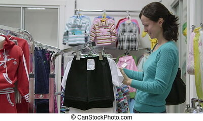 Woman looking for clothes in clothing store,  medium shot