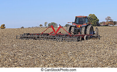 Red Farm Tractor - Red farm tractor tilling a field of corn...
