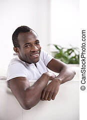 Men relaxing at home. Relaxed African descent men looking at...