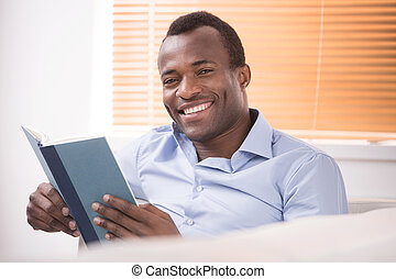 Reading an exciting book. Cheerful African descent reading a...