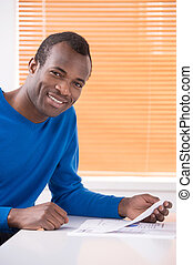 Paperwork. Cheerful African descent men holding paper in his hand and smiling at camera