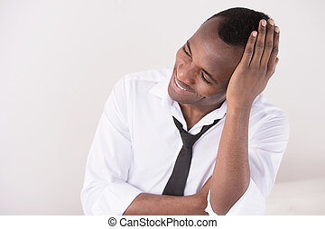 Happy businessmen. Happy African descent men sitting with his hand in hair and looking away