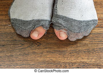 worn out socks with a hole and toes. - worn out socks with a...