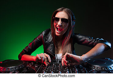 Female DJ. Happy young female DJ in sunglasses playing music...