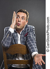 Surprised businessman - Handsome seated young businessman...