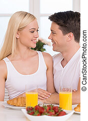 Having breakfast together. Young loving couple looking at each other while having breakfast together