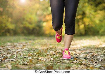 Autumn runner - Close up of feet of a runner running in...