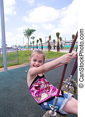 Beautiful girl play outdor on swing